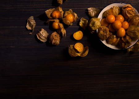 Dark moody food image of fresh ripe cape gooseberry on wooden table - still life photography. vintage style Stock Photo