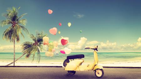 Motociclo giallo classico con palloncino di cuore sulla spiaggia cielo blu concetto di amore in estate e luna di miele matrimonio - effetto di colore vintage