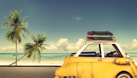 Travel destination: vintage car parked near the beach with bags on a roof - Honeymoon trip