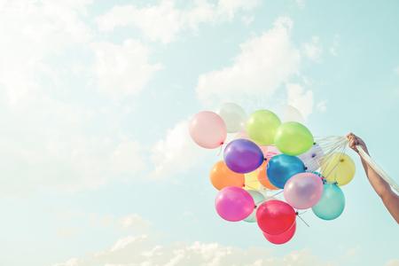Chica mano sosteniendo globos multicolores hechas con un efecto retro filtro de Instagram vintage, concepto de feliz cumpleaños en verano y fiesta de la luna de miel de la boda (el tono del color de la vendimia)