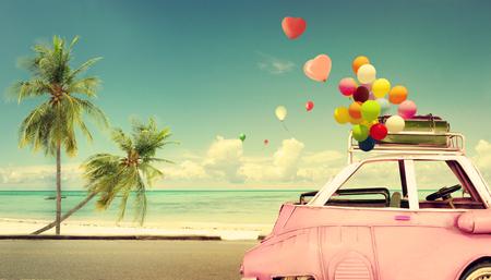 年份粉紅老爺車與沙灘藍天心臟五顏六色的氣球 - 夏季婚禮的愛情觀。蜜月之旅 版權商用圖片