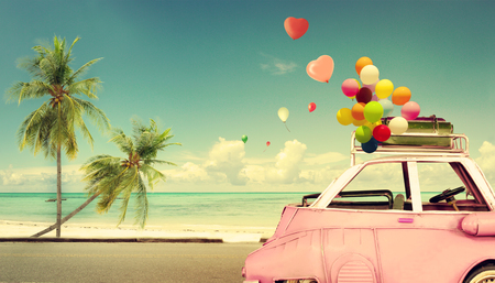 road of love: Vintage pink classic car with heart colorful balloon on beach blue sky - concept of love in summer and wedding. Honeymoon trip