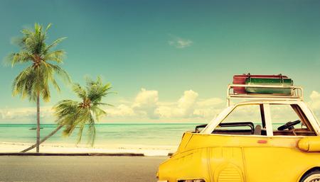 Resmål: tappning klassisk bil parkerad nära stranden med påsar på ett tak - smekmånad resa i sommar