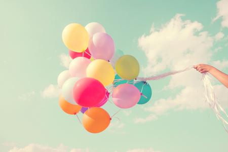 cielo azul: Niña de la mano que sostiene los globos multicolores hechas con un efecto retro filtro de la vendimia, el concepto de feliz cumpleaños en verano y fiesta de boda luna de miel (tono de color de época)