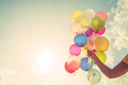 divercio n: Chica mano sosteniendo globos multicolores hechas con un efecto retro filtro de Instagram vintage, concepto de feliz cumpleaños en verano y fiesta de la luna de miel de la boda (el tono del color de la vendimia)