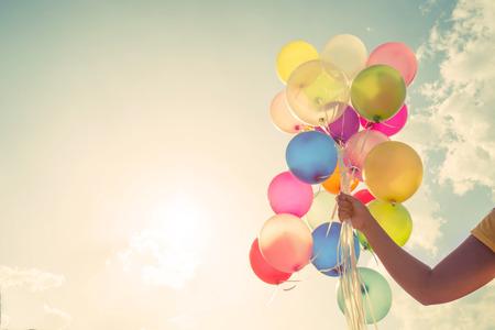 Dziewczyna ręka trzyma wielokolorowe balony zrobić z retro rocznika efekt filtra Instagram, pojęcie okazji urodzin latem i miesiąc miodowy Wesele (rocznik odcienia koloru)