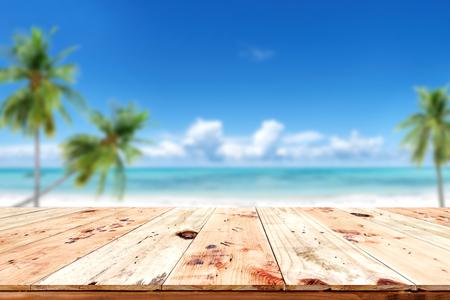Parte superiore della tavola di legno con sfondo sfocato del mare e del cielo blu - vuoto pronto per il vostro montage di esposizione del prodotto. Concetto di spiaggia in estate