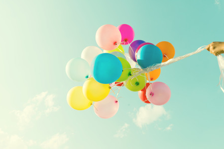 spaciousness: Girl hand holding multicolored balloons done with a retro vintage instagram filter effect, concept of happy birthday in summer and wedding honeymoon party (Vintage color tone)