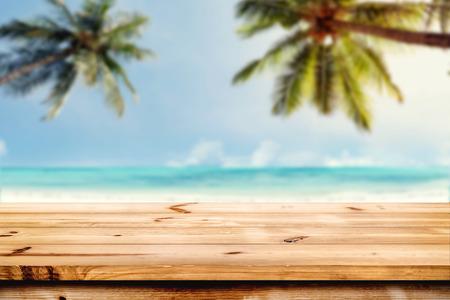 La parte superior de la tabla de madera con el mar y el fondo borroso cocotero - vacío listo para su montaje de la exhibición del producto. Concepto de la playa en verano