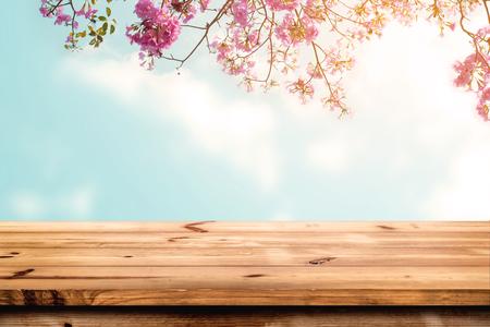 Överdel av träbord med rosa körsbärsblomblomma på himmelbakgrund - Tom redo för din produktvisning eller montage. Stockfoto