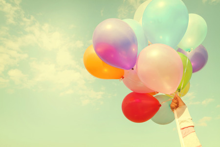 birth day: Girl hand holding multicolored balloons done with a retro vintage instagram filter effect, concept of happy birth day in summer and wedding honeymoon party (Vintage color tone) Stock Photo
