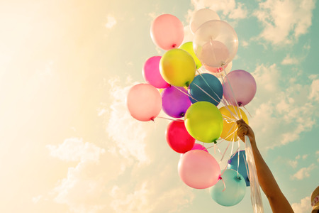 女孩手拿著五顏六色的氣球。快樂的生日聚會。復古濾鏡效果