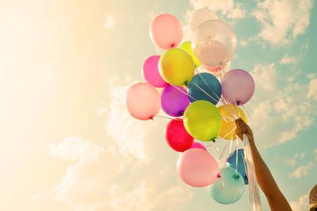 Meisje hand houden van kleurrijke ballonnen. happy birthday party. vintage filter effect