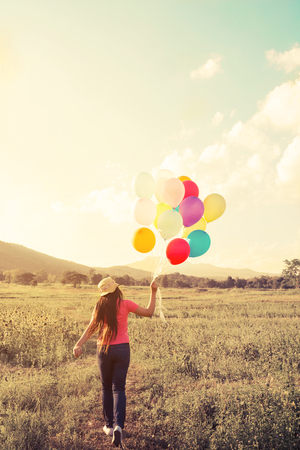 baloons: Happiness teen girl with colorful balloons enjoy in the sundown time at grassland. Happy birthday party. vintage color tone effect