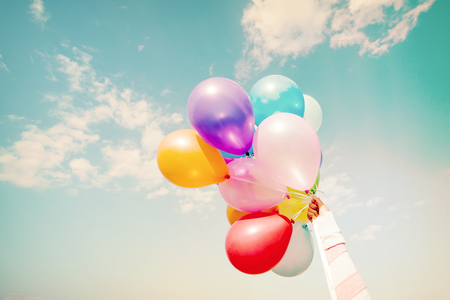 spaciousness: Girl hand holding multicolor balloons done with a retro instagram filter effect