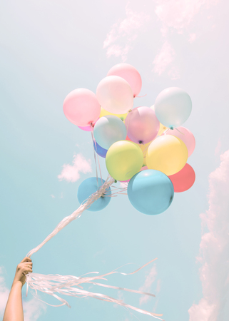 wishes romantic: Girl hand holding colorful balloons. happy birthday party. vintage pastel filter effect