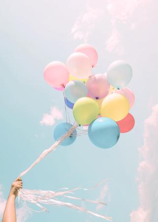 Mano de la muchacha que sostiene los globos coloridos. fiesta de cumpleaños feliz. efecto de filtro en colores pastel de la vendimia