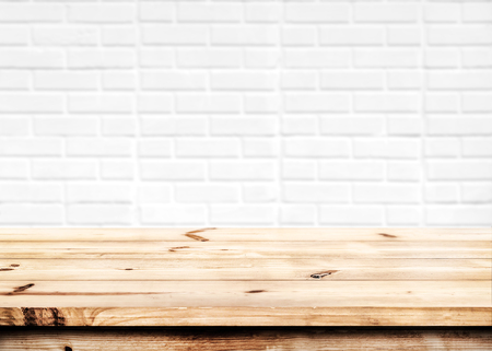 製品の配置やテーブルの白いレンガ壁の背景で、フォア グラウンド上に焦点を当てたモンタージュの空の木のテーブル。