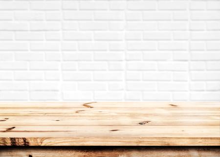 mesa de madera vacía para la colocación de productos o montaje, con especial atención a la superficie de la mesa en el primer plano, con fondo blanco de la pared de ladrillo. Foto de archivo