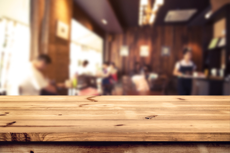 Top Holztisch Zähler mit verschwommenen Café (Café) und Restaurant-Shop unter Hintergrund - Leere Tabelle bereit für Ihre Produktpräsentation oder Montage. Vintage-Effekt Ton