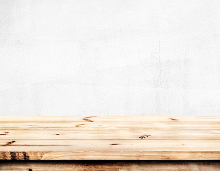Empty pine wood table top ready for your product display montage. with white wall background.