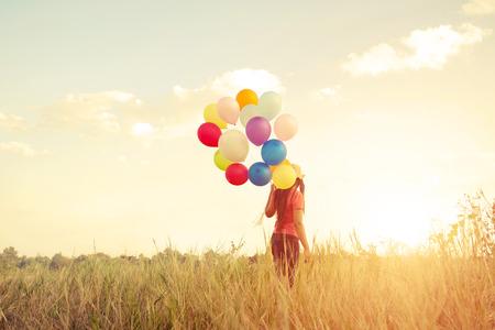 幸福年輕女孩與五顏六色的氣球在草原日落時間享受。快樂的生日聚會。復古色調效果