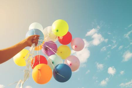 女孩手拿著一個復古濾鏡效果進行多色氣球,在夏季和新婚蜜月黨(復古色調)快樂誕生之日的概念 版權商用圖片