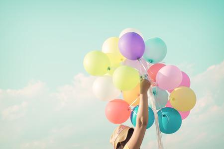 お祝いやライフ スタイル コンセプト - 夏休みにカラフルな風船を持つ美しい女性。パステル カラー フィルター