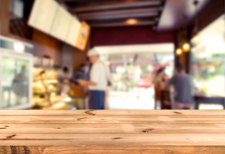 Top of wood table counter with blurred people in coffee shop (cafe) and restaurant shop interior background - Empty table ready for your product display montage.