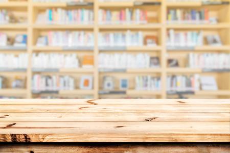 Lege houten tafelblad klaar voor uw product beeldscherm montage. met een boekenplank in de bibliotheek onscherpe achtergrond.