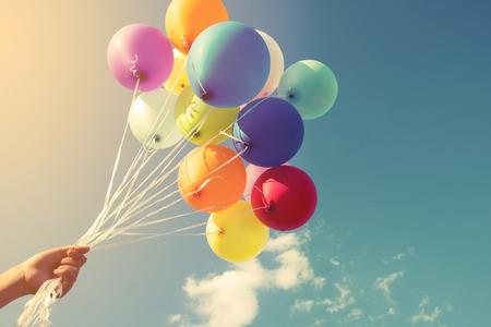 개념: 복고풍 인스 타 그램 필터 효과와 함께 할 여러 가지 빛깔의 풍선을 들고 소녀의 손, 여름 결혼식 신혼 여행 파티 (빈티지 색조) 행복 출산 일의 개념