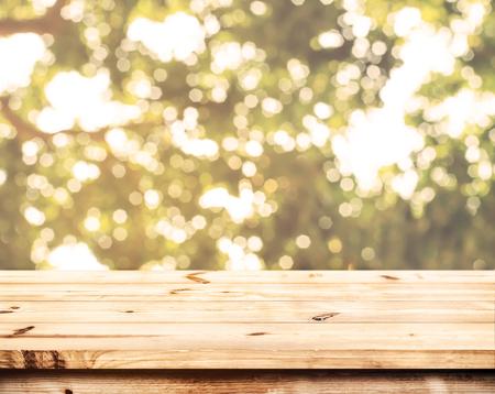 Arriba de la mesa de madera con el bokeh borrosa fondo de la naturaleza - vacío listo para su exposición del producto o montaje.