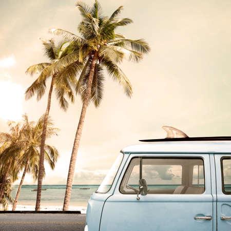 Vintage bil parkerad på tropisk strand (havet) med en surfbräda på taket
