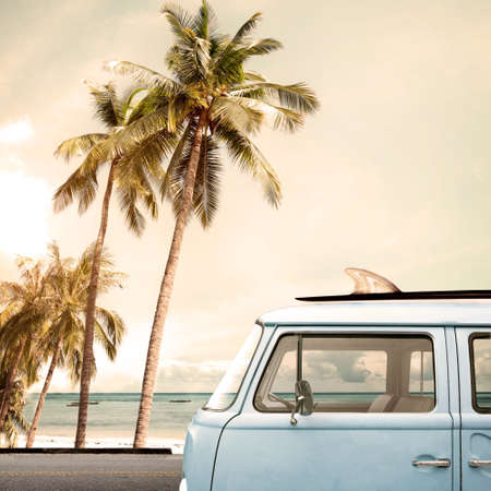 surfing: Vintage car parked on the tropical beach (seaside) with a surfboard on the roof Stock Photo