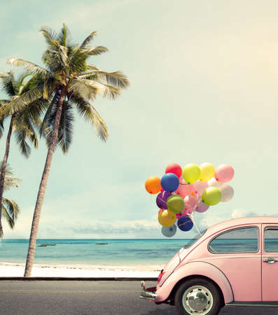 balloons: Vintage card of car with colorful balloon on beach blue sky concept of love in summer and wedding honeymoon Stock Photo