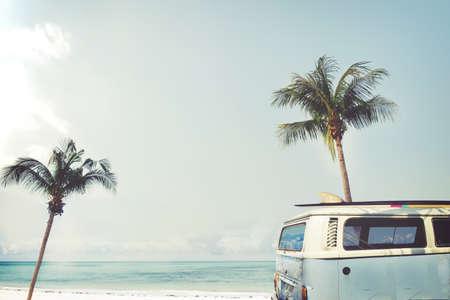 Oldtimer auf dem tropischen Strand geparkt (Meer) mit einem Surfbrett auf dem Dach - Urlaubsreise im Sommer