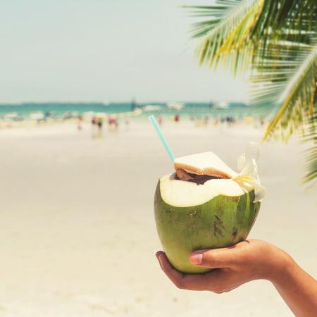 coco: cócteles de coco frescas con las manos en la mujer en la playa tropical - vacaciones en verano. estilos de color de la vendimia Foto de archivo