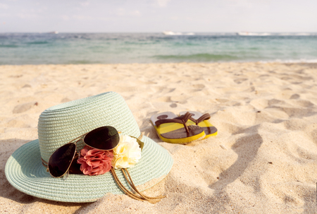flip flops: Summer vacation concept with straw hat, sunglasses and flip flops on sandy tropical beach - vintage color styles