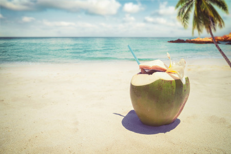 Fresh coconut cocktails with in on sandy tropical beach - vacation in summer. vintage color styles 스톡 콘텐츠