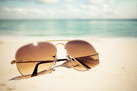 sandy beach: Sunglasses on sandy beach in summer - vintage color styles