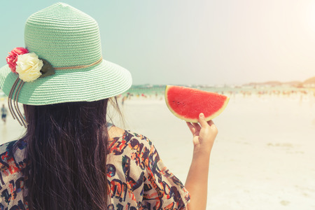 Rear of beautiful woman with fresh watermelon with in hands on tropical beach - vacation in summer. vintage color styles