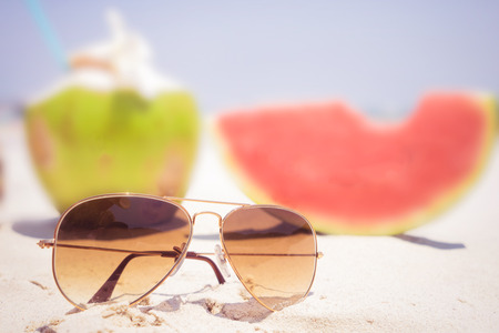 summer fruit: Summer vacation concept with sunglasses and fruit on sandy tropical beach