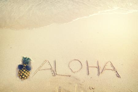 海の波 - 無料スペースで砂浜に書かれた碑文アロハ。ヴィンテージ色のトーン効果