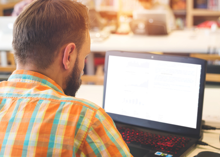 cropped image: Rear view of young business hipster man working on his laptop at office desk - cropped image composition with vintage filter effect Stock Photo
