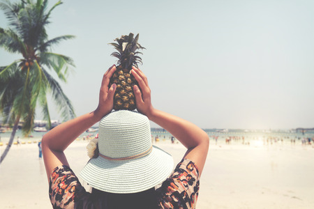 Fashion portrait rear of beautiful woman with fresh pineapple holds up - vacation on tropical beach in summer. vintage color styles