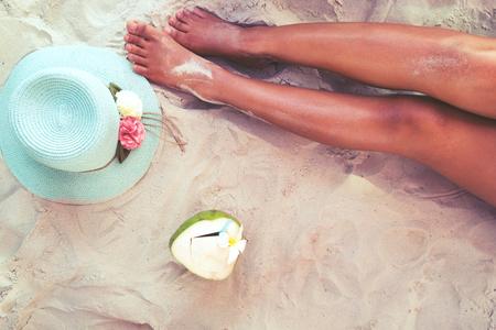 pies sexis: Tiempo libre en verano - hermoso de la mujer sexy bronceado. relajarse en la playa de arena con sombrero y cóctel de coco. estilos de color de la vendimia Foto de archivo