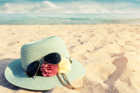 sand glass: Summer vacation concept with straw hat and sunglasses on sandy tropical beach - vintage color styles