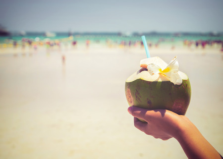 straws: Fresh coconut cocktails with in woman hands on tropical beach - vacation in summer. vintage color styles Stock Photo