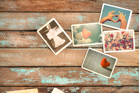 old photograph: Wedding, love and honeymoon instant photo album on wood table. paper photo of vintage camera - vintage and retro style
