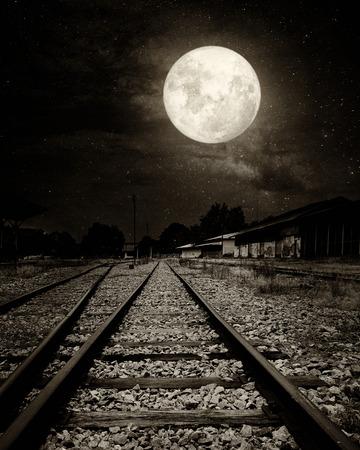 noche y luna: Hermoso campo de ferrocarril con la vía láctea estrella en cielos nocturnos, luna llena - obras de arte de estilo retro con el tono de color de la vendimia (estilos de efectos de filtro de grano de película vintage blanco y negro)